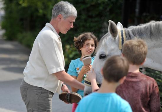 Claudia Pauel, Leiterin des Zentrums für Therapeutisches Reiten Köln, putzt gemeinsam mit Kindern ein Pferd.