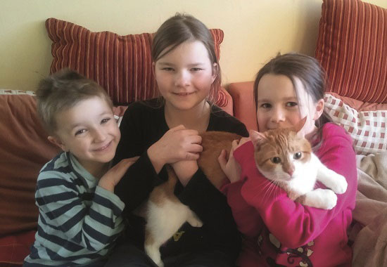 Die Kinder sind überglücklich, den lange verschwundenen Kater Findus wieder in die Arme zu schließen.