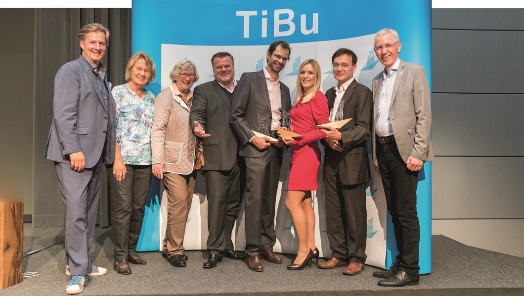 Die TiBu-Preisträger 2017, Stefanie Hertel (3. v. r.), Manfred Karremann (2. v. r.) und Dr. Reinhold Hartmann (4. v. r.), zusammen mit dem Präsidium und Moderator Attila Weidemann (1. v. l.).